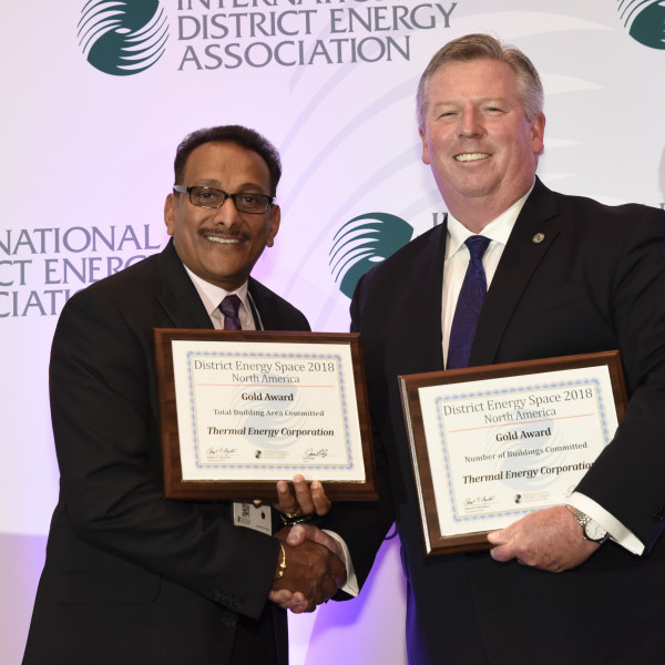 Ram Goonie, left, accepts TECO's District Energy Space Gold Awards from IDEA's Rob Thornton.